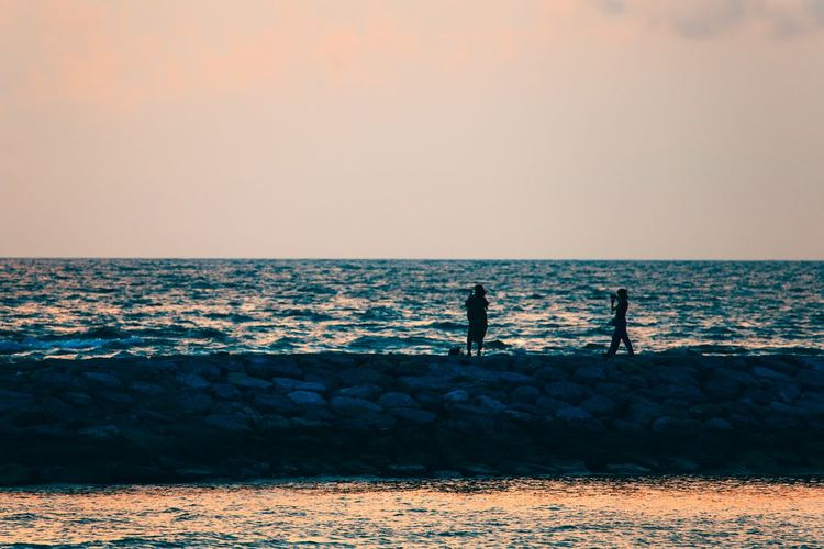 Silhouette men fishing on beach against clear sky