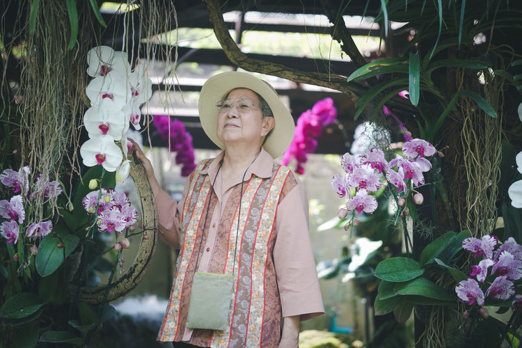 Portrait of woman standing by pink flowering plants