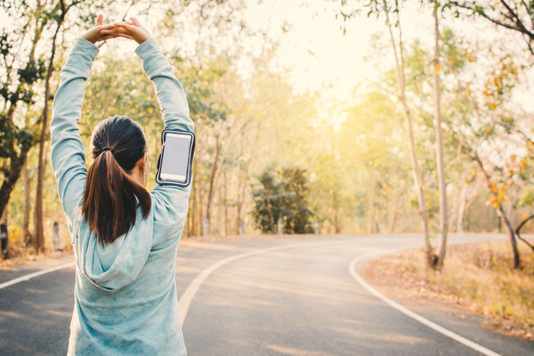 Woman exercising on road against trees