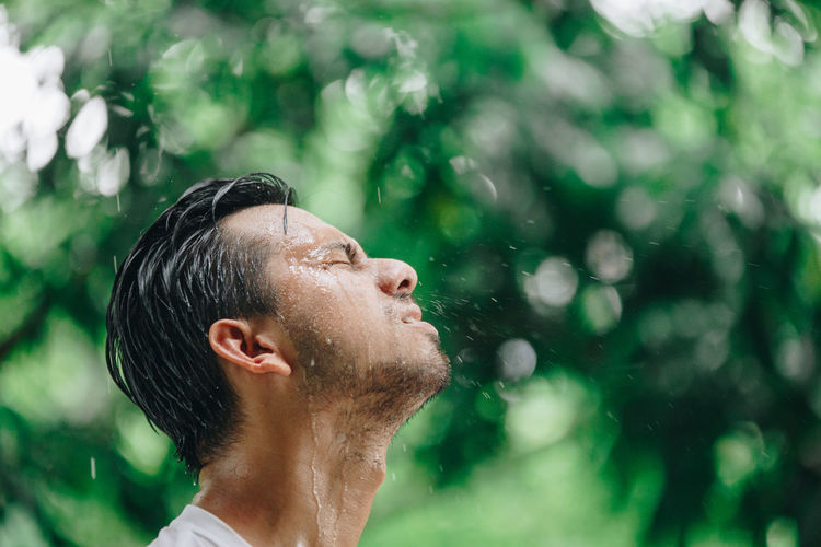Real People Lifestyles Headshot Men One Person Focus On Foreground Leisure Activity Wet Nature Males  Portrait Looking Young Adult Day Eyes Closed  Side View Young Men Water Outdoors Rain