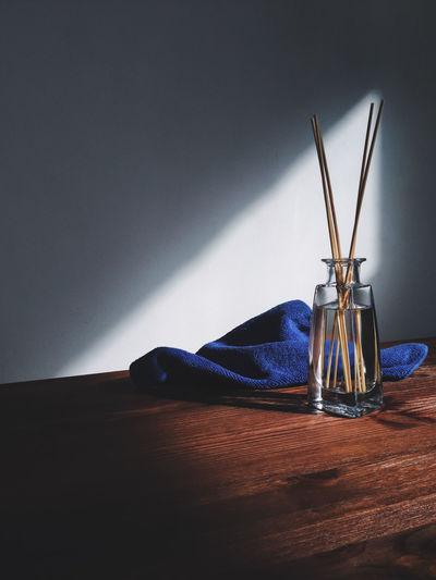Sticks in vase by towel on hardwood floor