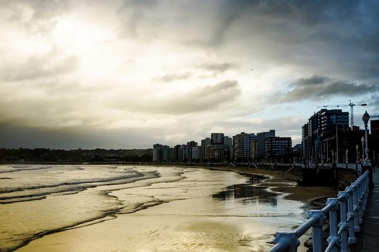 Buildings by sea against sky in city