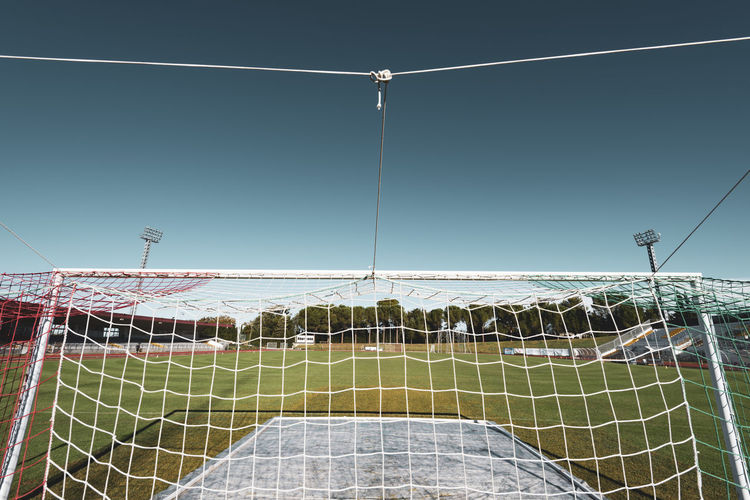 soccer field goal from behind No People Sport Football Soccer Field Net - Sports Equipment Sunlight Soccer Connection Grass Absence Netting Low Angle View Day Outdoors Playing Field Games Goal Post Goal Floodlight Stadium Empty Urban City Competition Day Team Sport Supporters From Behind