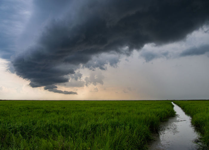 Scenic view of agricultural field against storm clouds