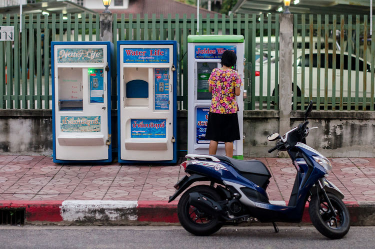 Woman buy water from Automatic vending drinking water Automat Automatic Vending Business Buying Drinks Composition Drink Water Information Land Vehicle Machine Mode Of Transport Motor Scooter Motorcycle Package Technology Text Transportation Vending Machine Waiting