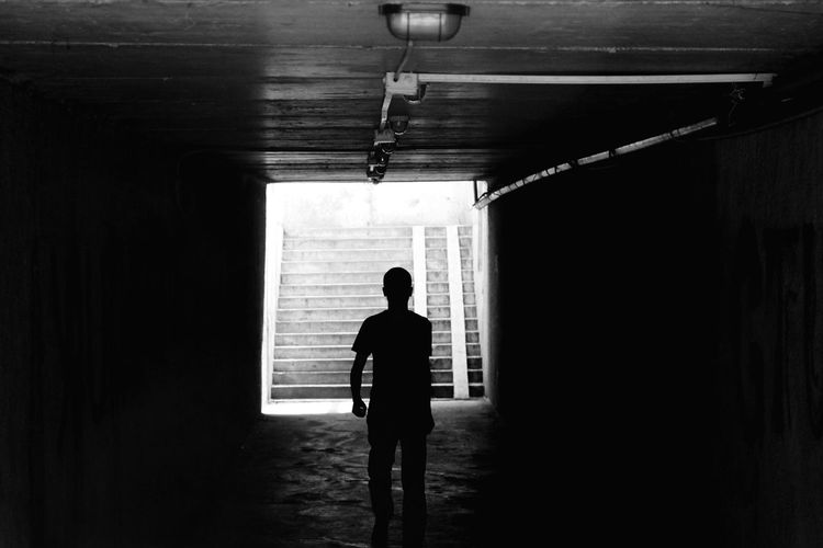 Silhouette Man Walking In Underground Walkway