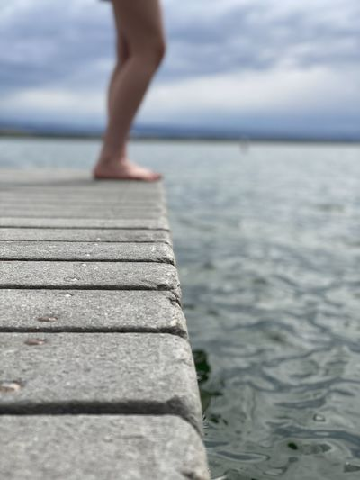 Tranquil setting of barefoot person on pier with horizon in the distance
