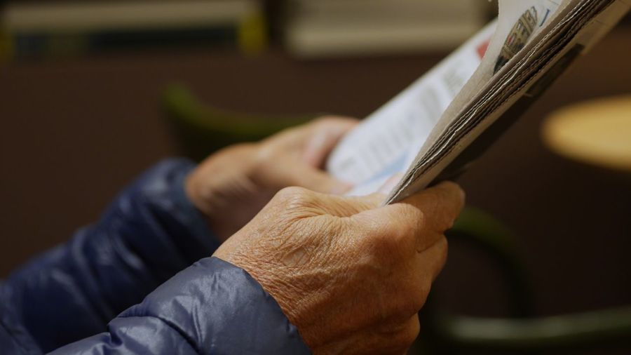 Cropped wrinkled hands of person holding newspaper
