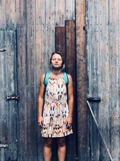 Portrait of woman standing on wooden door
