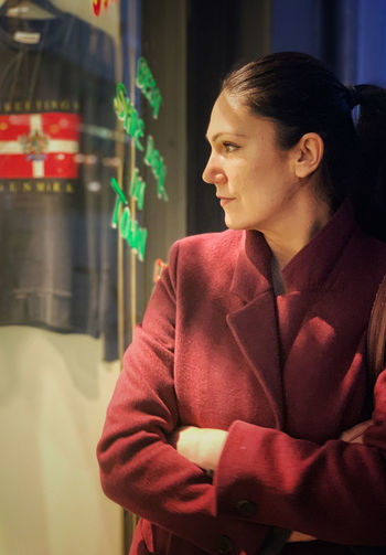 A young woman in front of a shop, shopping, city, elegant, stylish, cold temperature, glass material