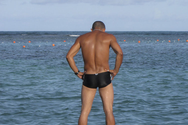 Rear View Of Shirtless Man With Hand On Hip Standing On Sea Against Sky