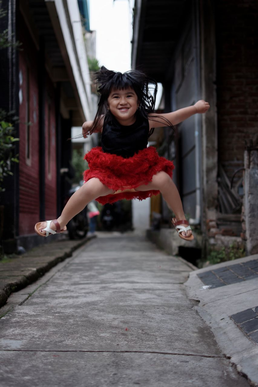 Portrait Of Smiling Girl Jumping On Street