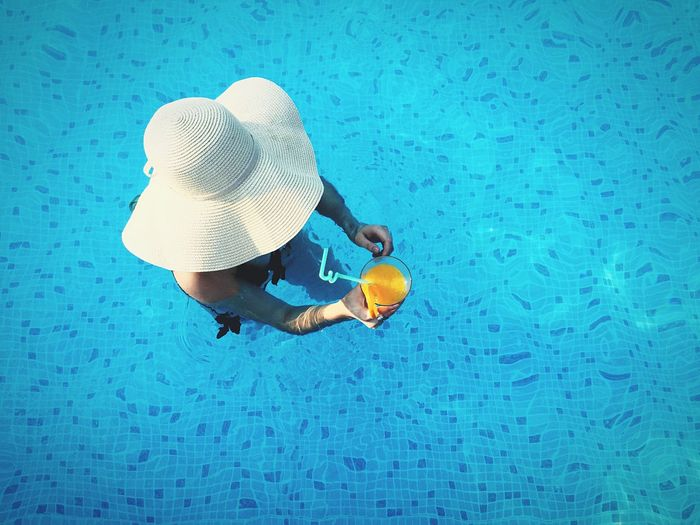 Pool Summer Girl Hat Drinks Orange Juice  Blue Water From Above  The Portraitist - 2016 EyeEm Awards TakeoverContrast Neon Life