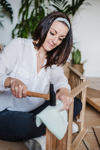 Young woman sitting on chair at home