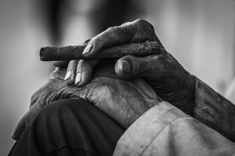 Close-up of senior man holding cigar