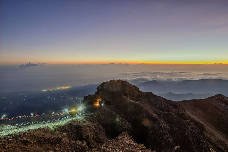Light trails on summit mount rinjani against majestic sky
