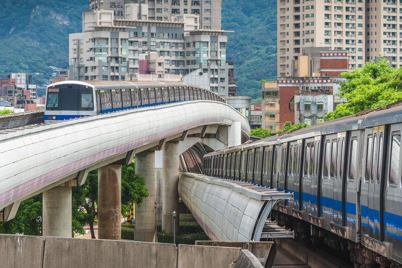 Train on bridge by buildings in city