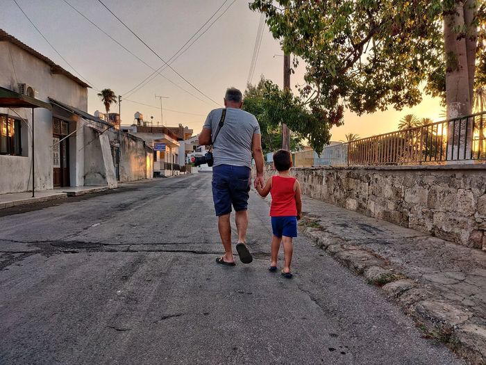 Rear view of father and son walking on city street