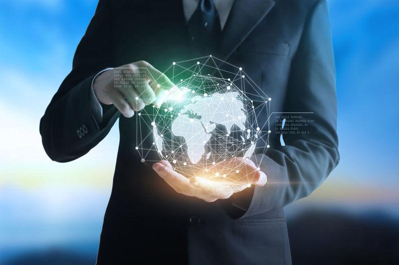 Digital composite image of businessman holding globe
