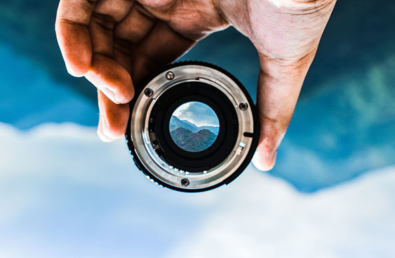 Upside down image of person holding camera lens against mountain