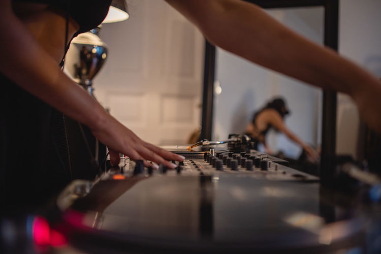 Midsection of woman playing sound mixer at home