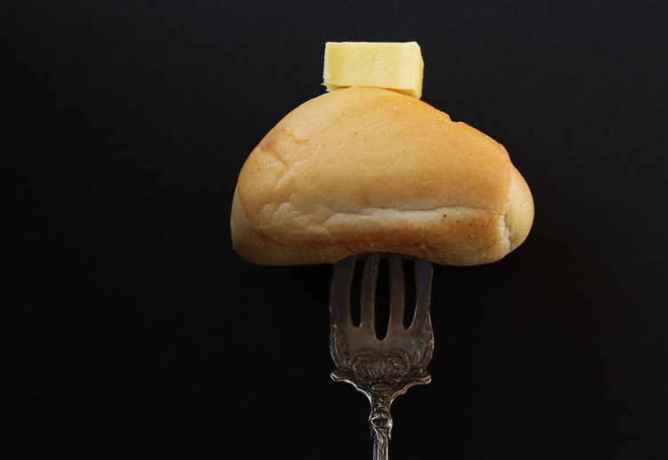 Bread and butter Copy Space Eating Fork Meal Roll Wheat Black Background Bread Bread And Butter Butter Close-up Dairy Product Dark And Moody Fine Dining Food And Drink Freshness Gluten No People Still Life Studio Shot