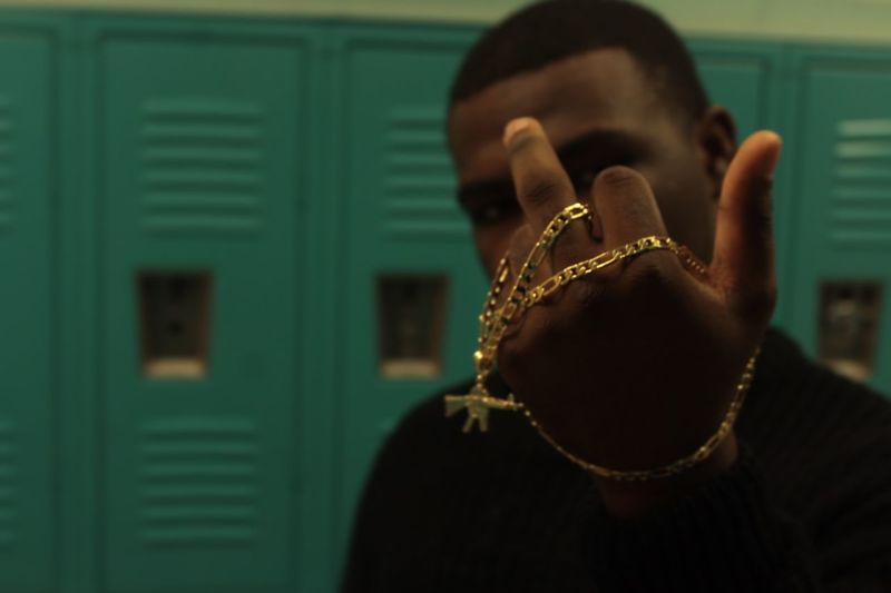 Man with gold chain showing middle finger