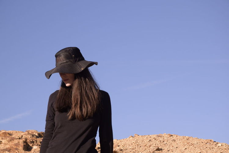 Woman wearing hat standing against clear blue sky