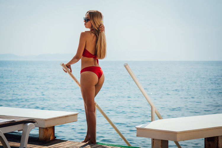 Sensuous woman standing by sea against sky
