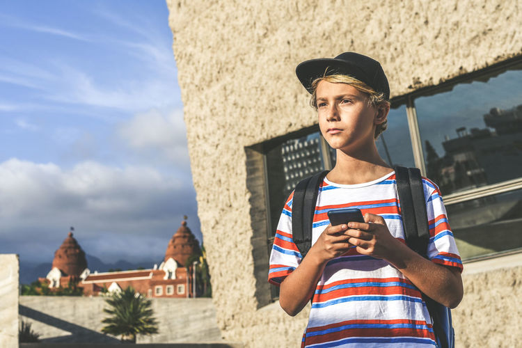 Boy holding phone while standing outside building on sunny day