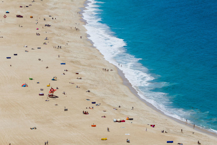 High angle view of people lying on beach with blue sea