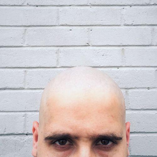 Portrait Of Bald Man Against Brick Wall