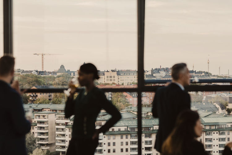 People standing by cityscape against sky seen through window
