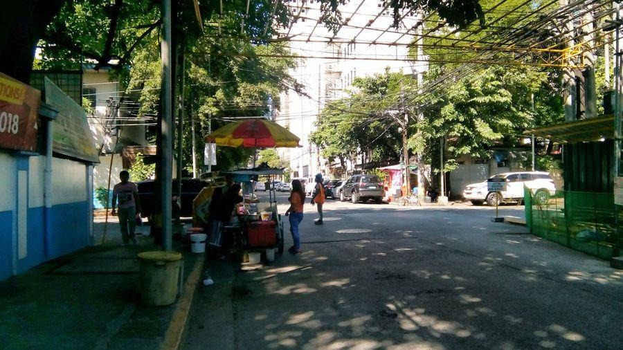 People walking on sidewalk by street in city