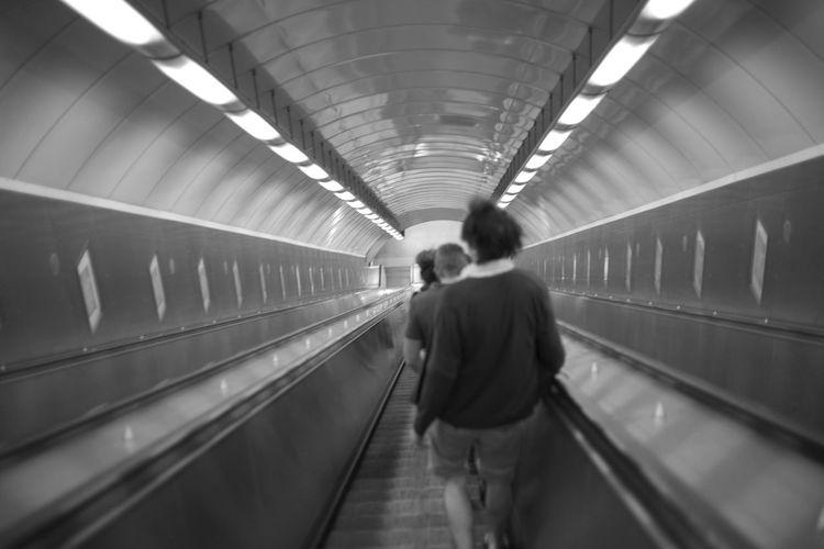 Rear view of man walking on escalator at subway station
