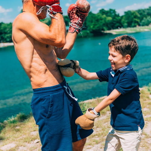 Small Boxer With Senior Trainer Boxing Boxing Gloves Boxing Training Boxing Match Boxing Man Boy Outdoors Boxing Sparring Sport Boxing Class Senior 60s 6-7 Years Men Kid Family Grandson Grandfather Trainer Training Boxer Fighter Smiling Happy Lake