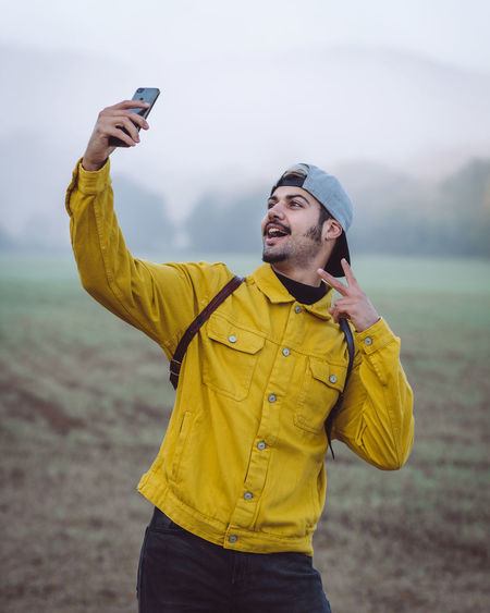 Young man photographing with mobile phone