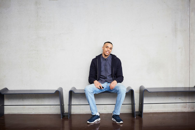 Portrait of young man sitting on chair against wall