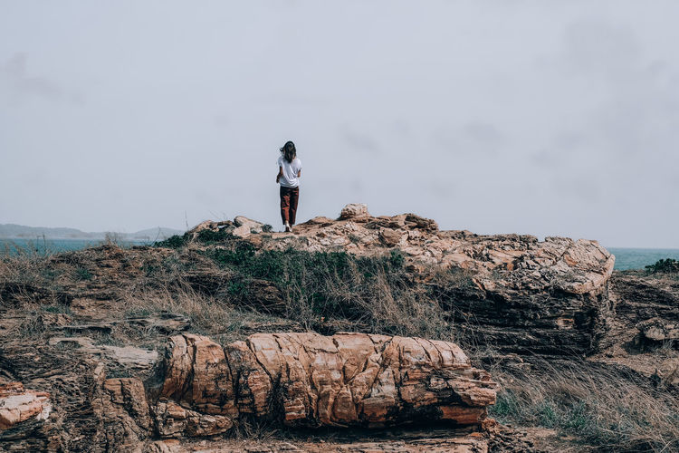 Full length of woman standing on rock against sky