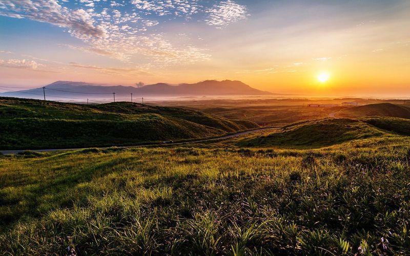 Idyllic shot of green landscape against sky during sunset