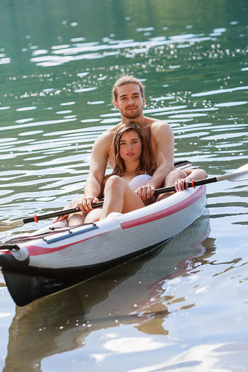 Portrait of couple sitting in boat on lake