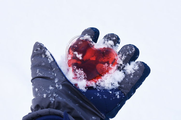 Cropped Hand Holding Heart Shape And Snow During Winter