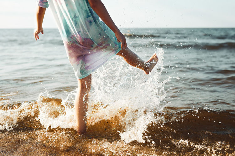 Girl spending a free time jumping splashing in a sea on a beach at sunset during summer vacation