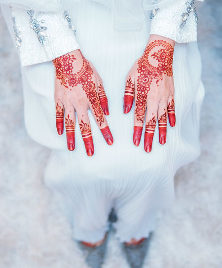 Low Section Of Bride With Henna Tattoo On Hands