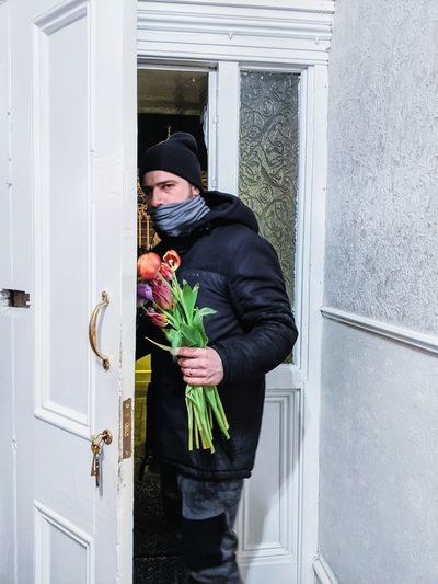 Man holding bouquet and standing at doorways