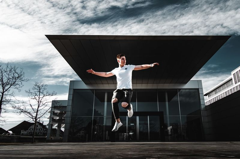 Man jumping on built structure against sky