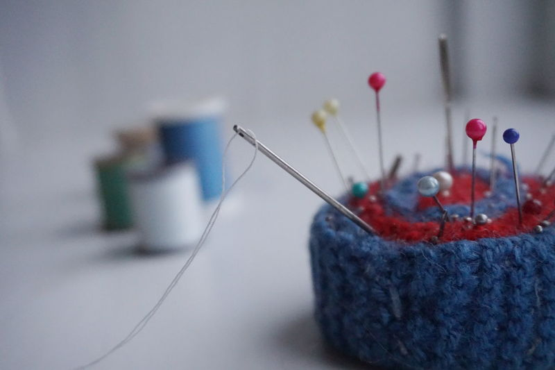 Close-up of pin cushion with colorful pins on table