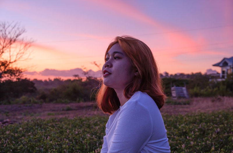 Portrait of young woman sitting on field against sky during sunset