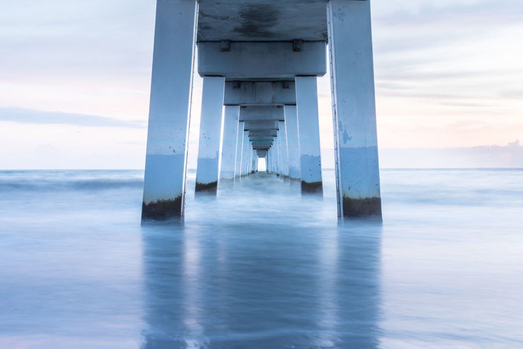 Long Exposure Image Of Bridge In Sea Against Sky During Sunset