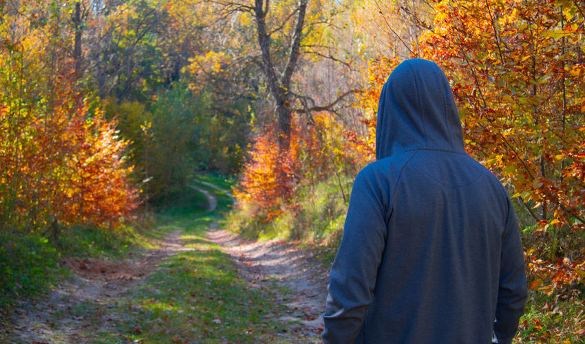 Rear view of man in hood standing at forest during autumn